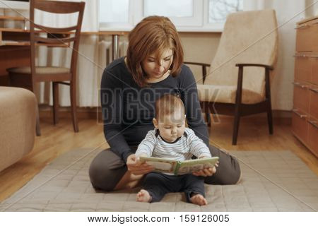 Mother Reading A Book With Her Baby