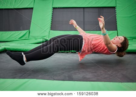 Young woman jumps on trampoline attraction in lying position.