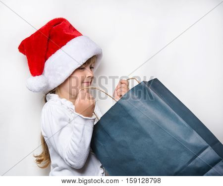 young maiden in a red cap looking for the gifts