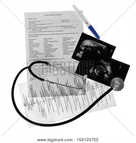 Ultrasound scan of baby and stethoscope on white background