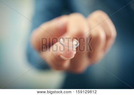Contact lens on female finger, close up view. Medicine and vision concept