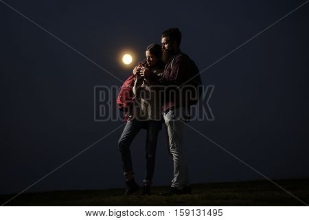 couple of strong man hipster with long beard and moustache in checkered shirt and sexy woman or cute girl with backpack on twilight embracing on darkness