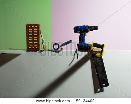 Technical or construction tools drill saw trowel brick brush blank paper and insulating tape for copy space on colorful background