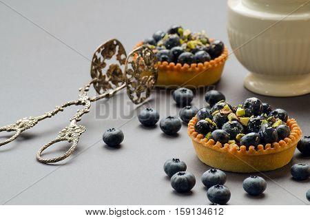 Cake with blueberries vintage tongs dessert and milk jug