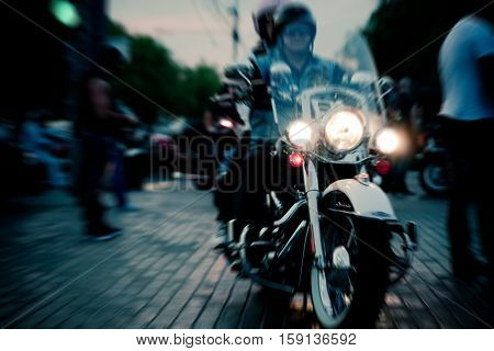 Couple of Bikers on Evening City Road Sidewalks. Motion Effect Applied. Humans Not Recognizable. Image May Be Used in Article About Biker Club Meeting in Metropolis.