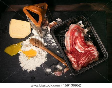 Crude products on a kitchen table. Crude bacon the broken egg and flour. On a background a grater and cheese on a flour hill a wooden spoon. Products against a dark background