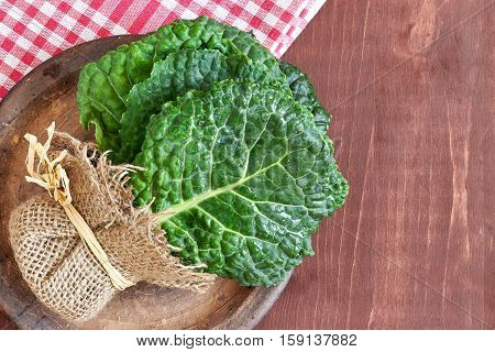 Raw organic savoy cabbage leaves on wooden background. Top view with copy space