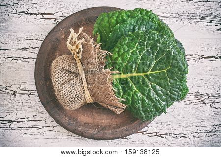 Raw organic savoy cabbage leaves on white rustic wooden background. Top view