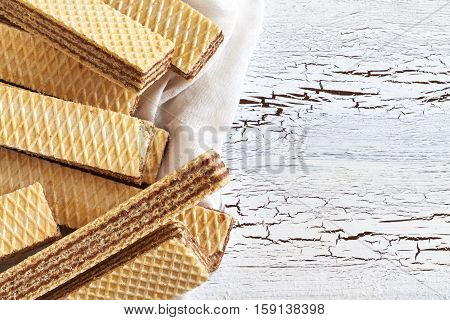 Wafer biscuits with chocolate cream on white rustic wooden background. Top view with copy space