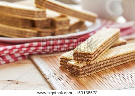 Wafer biscuits with chocolate cream on wooden table
