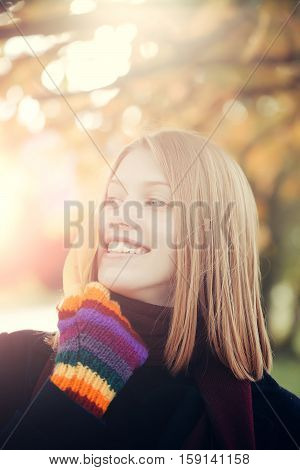 Pretty happy cute girl or young beautiful woman with blonde hair and yellow leaves outdoors in autumn park on natural background in colorful gloves