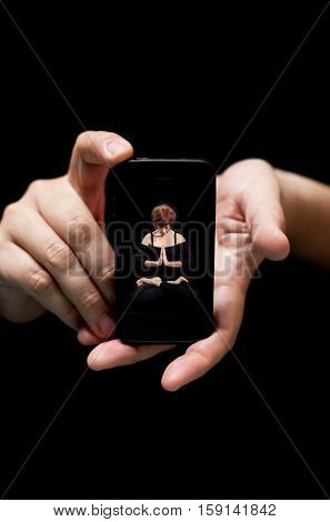 Hands Holding Smartphone showing a Genie woman meditating in black concept of technology at your services (on black background with very shallow depth of field)