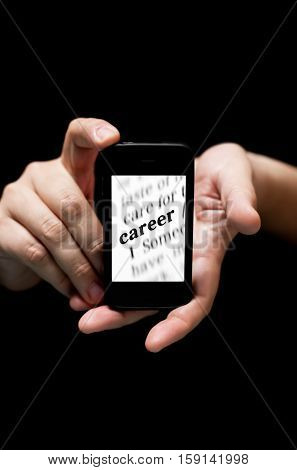 Hands Holding Smartphone showing the Word Career printed concept of finding jod online (on black background with very shallow depth of field)