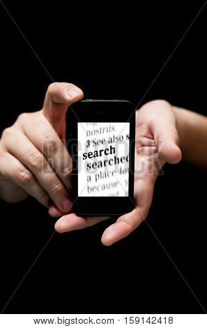 Hands Holding Smartphone showing the Word Search printed concept of finding anything online (on black background with very shallow depth of field)