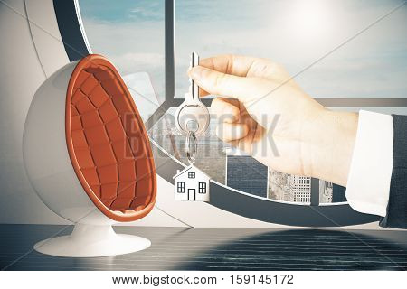 Hand holding key with house keychain on modern interior background. Real estate concept. 3D Rendering