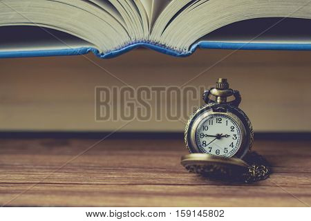 Pocket Watch in Front of Book with Blank Space in Vintage Tone