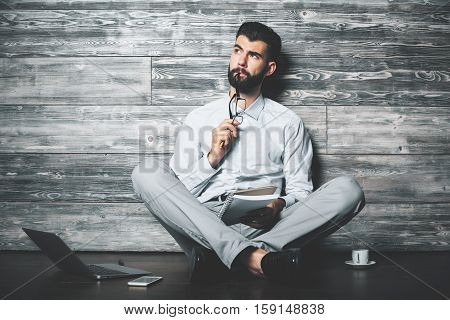 Attractive european boy with notepad sitting on wooden floor with laptop smartphone and coffee cup. Young author