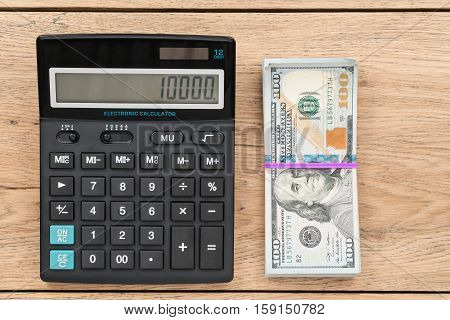 Big black calculator and dollars bundle tied with a rubber band lying on an old wooden table