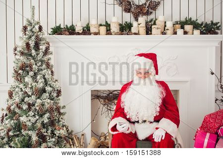Grumpy Santa leaning exhausted on his office desk