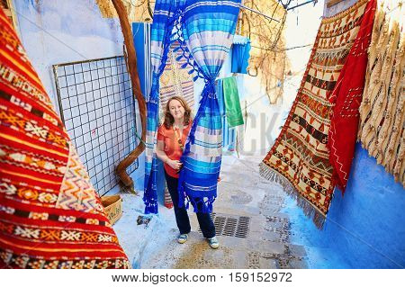 European tourist on a street carpet market in Chefchaouen Morocco small town in northwest Morocco known for its blue buildings