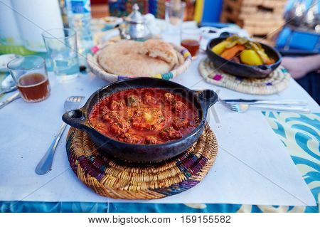 Traditional Moroccan dish kefta tajine with meat balls and baked egg in tomato sauce
