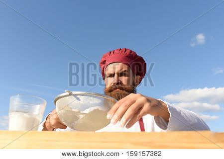 Man cook chef with beard on handsome face in white and red uniform cooking dough with strainer sunny outdoor on blue sky background