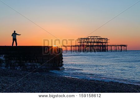 Person practicing Tai Chi at sunrise near West Pier Brighton.
