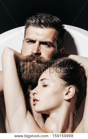 Bearded man hipster with beard and moustache and pretty girl sexy beautiful woman young sexi couple in love relax in bath on dark background
