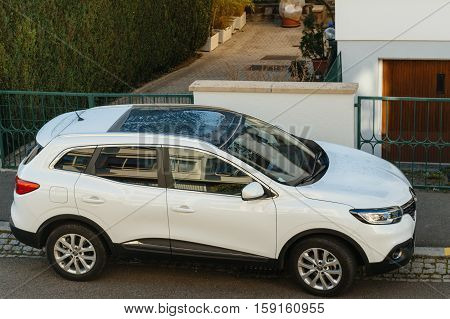 STRASBOURG FRANCE - NOV 29 2016: Aerial view of a white Renault Kadjar SUV car parked near a beautiful house. Renault is the bigest French automobile maker