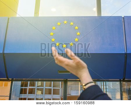 Elegant Woman hand trying to hold the stars of European Union insignia in front of the Council of Europe entrance