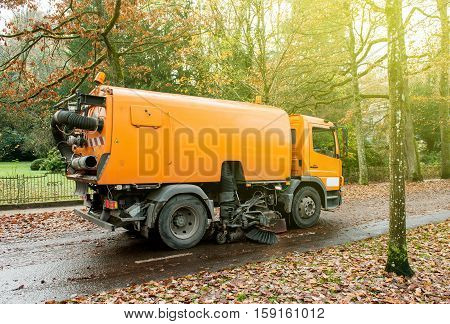 Orange Bucher CityFant 60 street sweeper machine cleaning the street after in fall from fallen foliage on a sunny day
