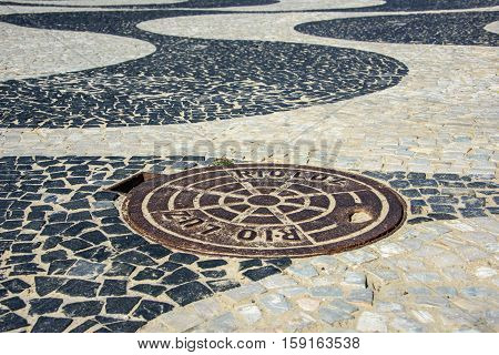 26 November 2016, Rio de Janeiro, Brazil. Black and white iconic mosaic Portuguese pavement by old design pattern with a manhole of Rio Luz at Copacabana Beach