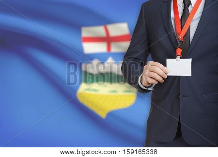 Businessman Holding Badge On A Lanyard With Canadian Province Flag On Background - Alberta
