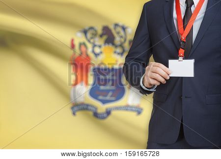 Businessman Holding Badge On A Lanyard With Usa State Flag On Background - New Jersey