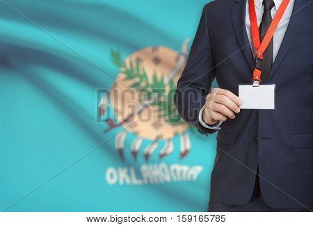 Businessman Holding Badge On A Lanyard With Usa State Flag On Background - Oklahoma