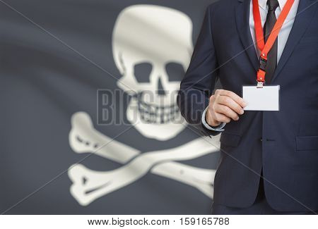 Businessman Holding Badge On A Lanyard With Flag On Background - Jolly Roger - Symbol Of Piracy