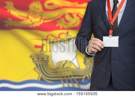 Businessman Holding Badge On A Lanyard With Canadian Province Flag On Background - New Brunswick