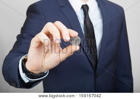 Businessman In Suit Holding 25 Us Cents Coin In Hand