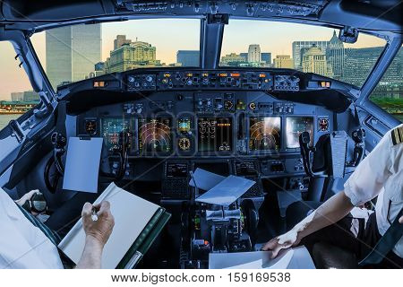 Airplane cockpit flying on New York City with World Trade Center and Twin Towers, Manhattan, United States, with pilots arms and blank white papers for copy space.