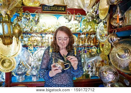 European tourist selecting a traditional teapot on Moroccan market (souk) in Fes Morocco