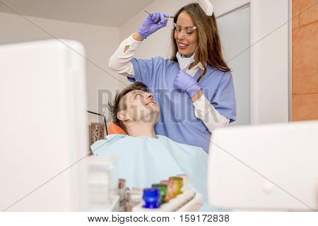 Young man having medical checkup in the dentist office by the young doctor
