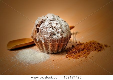 sweet cupcake with sugar on wooden cochleare and board background