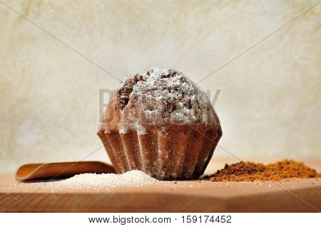 sweet fresh cupcake with sugar and cochleare on wood background