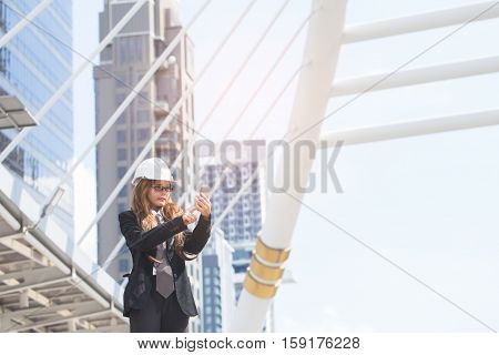 Middle-aged Engineer woman holding smart phone wearing construction hard hat or helmet. Middle-aged women professional standing in central of city