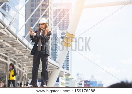 Middle-aged Engineer Woman Holding Smart Phone Wearing Construction Hard Hat Or Helmet. Middle-aged