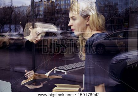 Two young professional women are reading in a library. Look outside the window. Education concept