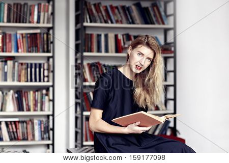 Beautiful blonde woman smiling with a book in a public library. Red lips, long white hair