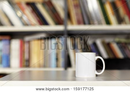 Blank white cup, design layout. Library interior