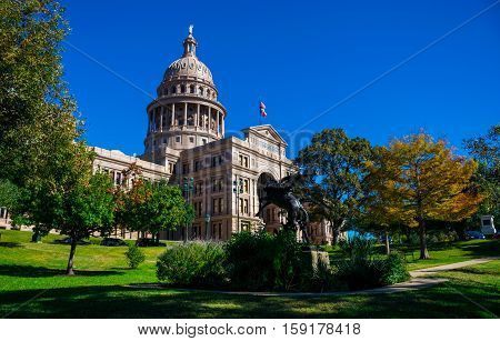 Texas State Capitol Building during sunny morning with Fall colors autumn leaves changing colors of leaves Austin Texas USA
