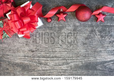 Christmas gift box decorate with red ribbon and ornament on wood background with copy space